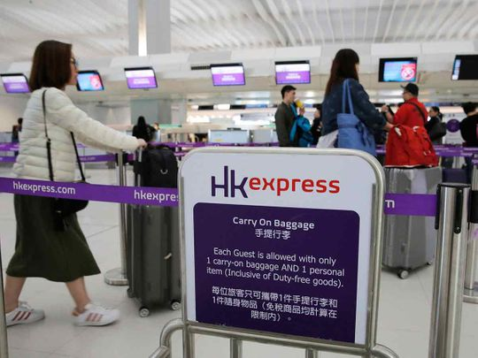 Passengers wait at the check-in counter of Hong Kong Express Airways at the Hong Kong International Airport.