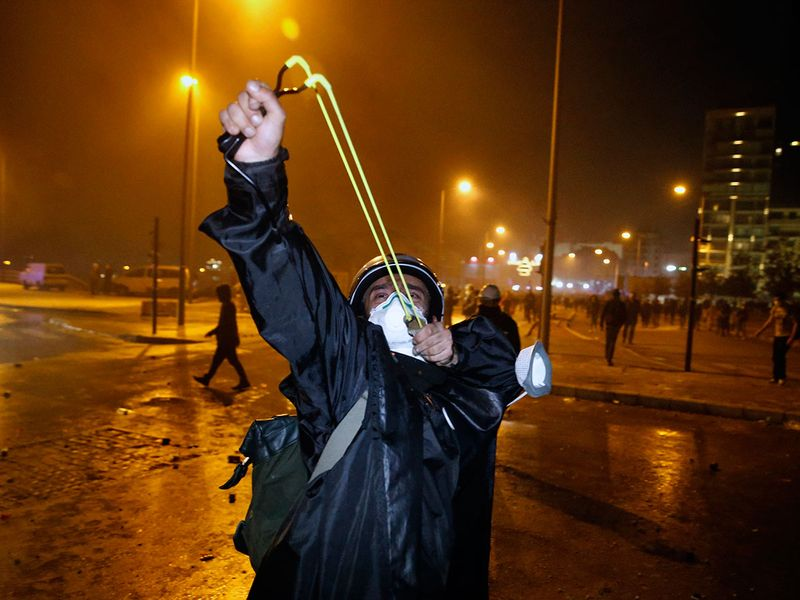 An anti-government demonstrator uses a slingshot toward the Lebanese riot police, during an anti-government protest in Beirut, Lebanon.