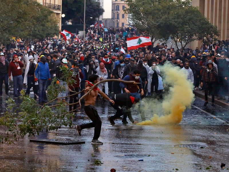 Anti-government demonstrators clash with riot police at a road leading to the parliament building in Beirut, Lebanon.