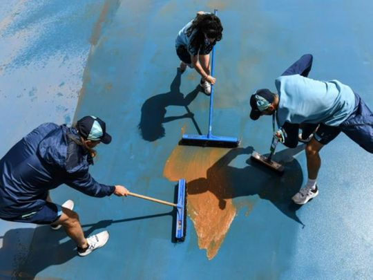 Workers attempt to clear mud off the courts at the Australian Open in Melbourne