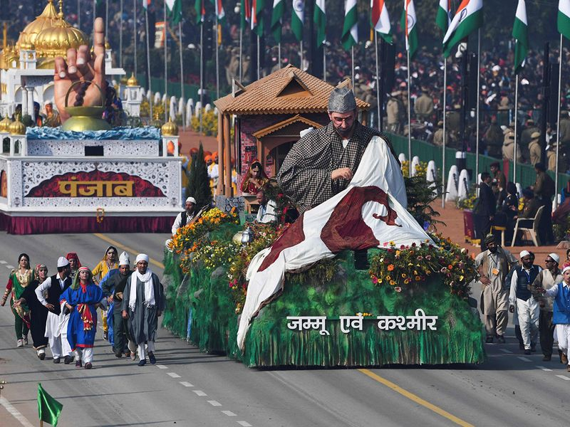 Performers walk next to a float representing Jammu and Kashmir along Rajpath during the Republic Day parade in New Delhi on January 26, 2020.