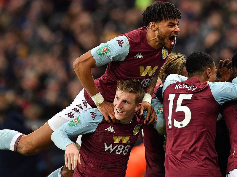 Aston Villa's English defender Tyrone Mings (L) celebrates with teammates after Aston Villa's Egyptian midfielder Trezeguet scores his team's winner.