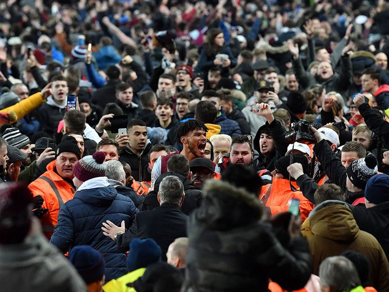 Aston Villa's English defender Tyrone Mings is mobbed by fans during a pitch invasion after the English League Cup semi-final second leg football match between Aston Villa and Leicester City at Villa Park in Birmingham.