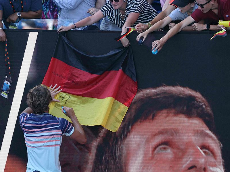 Germany's Alexander Zverev signs autographs after winning his men's singles quarter-final match against Switzerland's Stan Wawrinka.