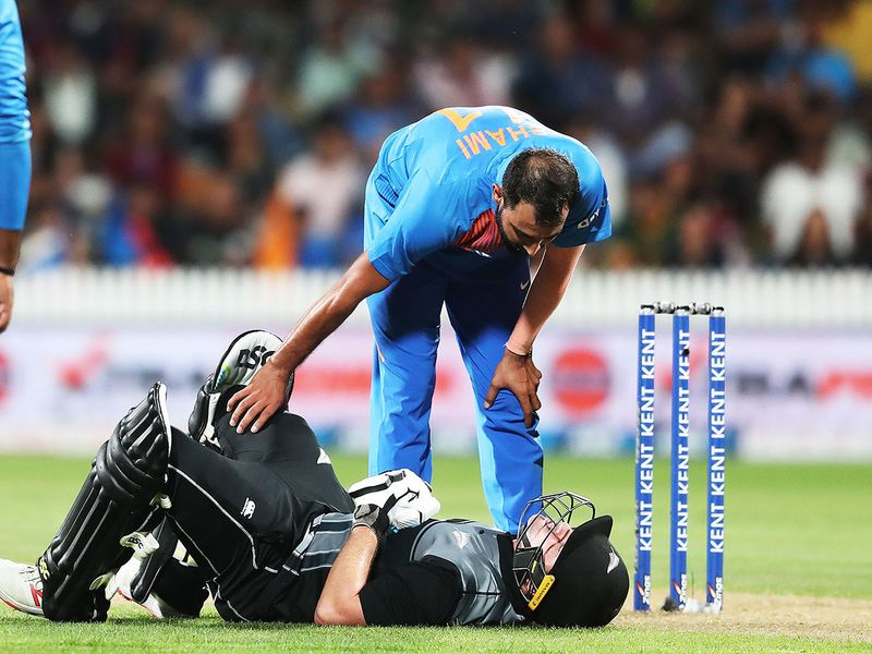 New Zealand's Colin Munro reacts after being hit by the ball as India's Mohammed Shami looks on.