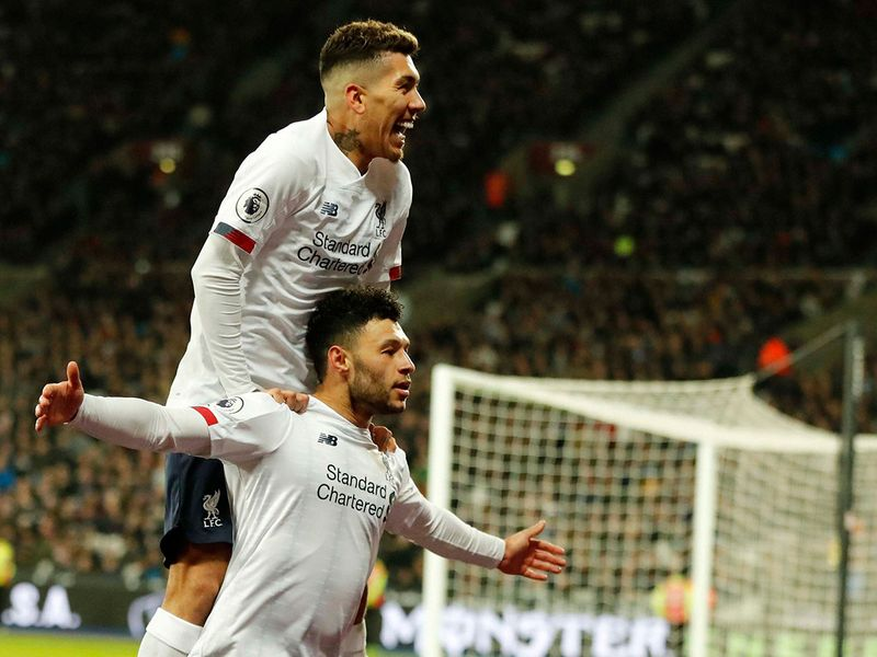 Liverpool's Alex Oxlade-Chamberlain, bottom, celebrates with Roberto Firmino after scoring his side's second goal against West Ham
