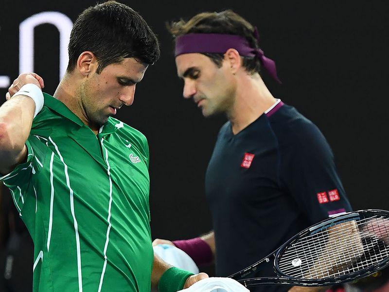 Serbia's Novak Djokovic (L) walks past Switzerland's Roger Federer during their men's singles semi-final match