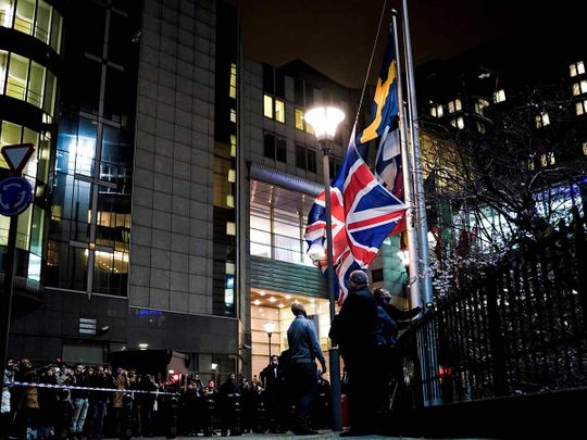 People take down the United Kingdom's flag from outside the European Union Parliament in Brussels,on Brexit Day, January 31, 2020
