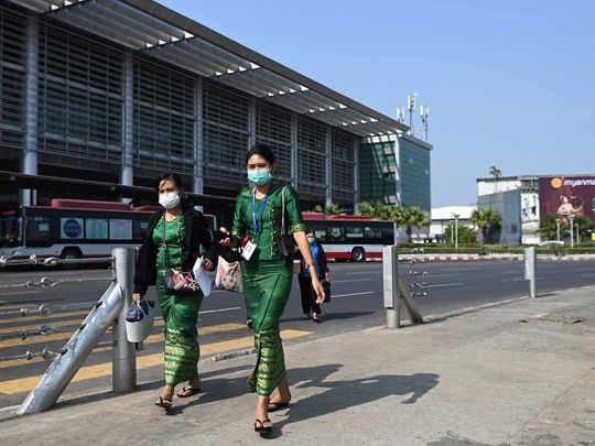 People wear protective facemasks outside the Yangon international aiport in Yangon on January 31, 2020.