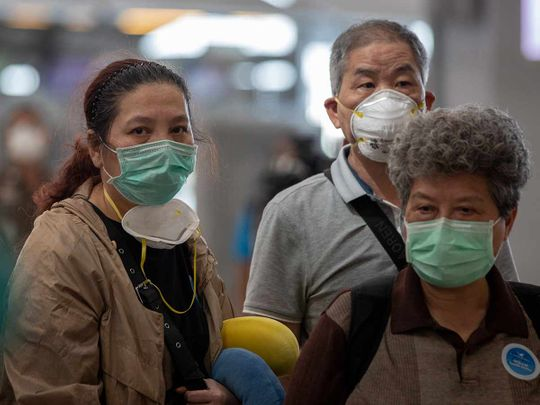 Tourists from Wuhan, China, some with double face masks, stand in a line for a charter flight back to Wuhan at the Suvarnabhumi airport, Bangkok, Thailand, Friday, Jan. 31, 2020.