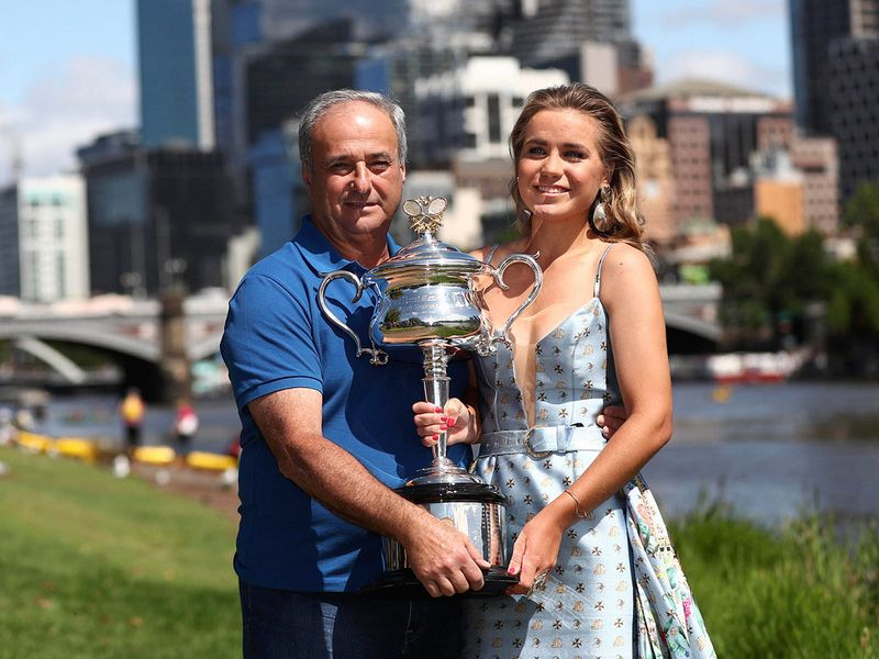 Sofia Kenin and her father Alex hold the Daphne Akhurst Memorial Cup at a photo shoot on the Yarra River following her win over Spain's Garbine Muguruza in women's singles final of the Australian Open