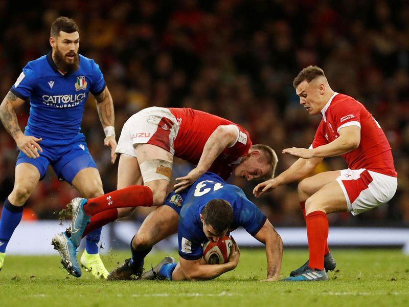 Italy's Luca Morisi in action with Wales' Nick Tompkins and Jarrod Evans