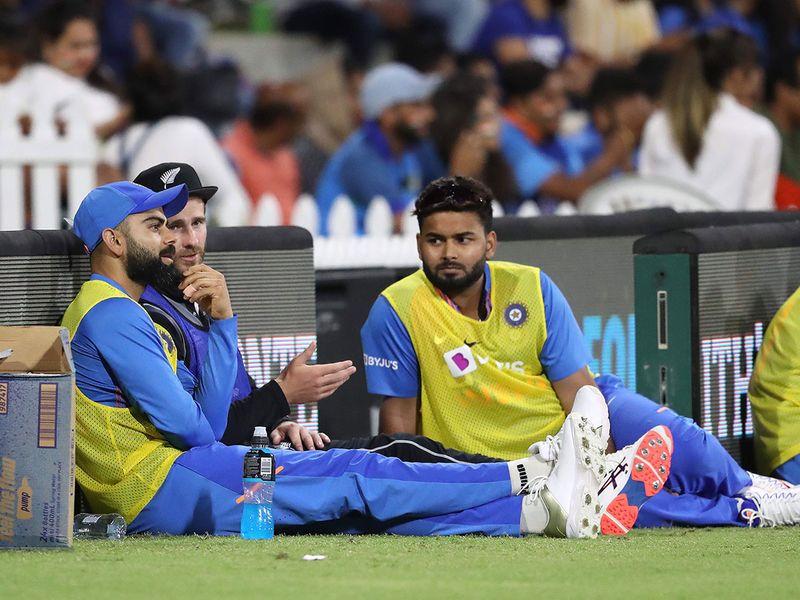 New Zealand captain Kane Williamson (C) talks with India's captain Virat Kohli (L) and Rishabh Pant