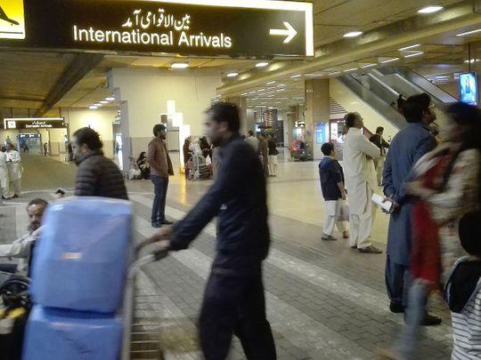 Passengers walk after  their arrival at the Jinnah International Airport in Karachi