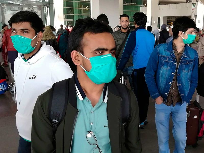 Pakistani students wearing protective facemasks come out upon their arrival from China at the Islamabad International Airport in Islamabad on February 3, 2020.
