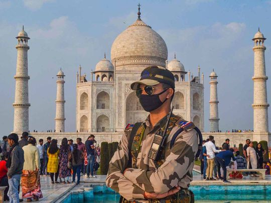 A CISF officer, wearing protective face mask, stands in the backdrop of the Taj Mahal, in Agra, Tuesday, Feb. 4, 2020.