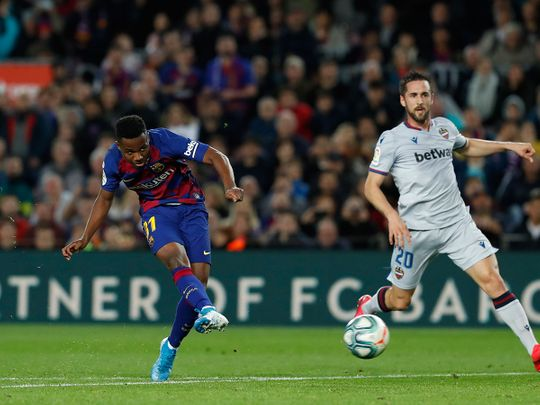 Barcelona's Ansu Fati, left, shoots to score his side's opening goal during a Spanish La Liga soccer match between Barcelona and Levante