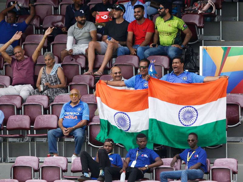 Indian supporters hold India's national flags during the match.