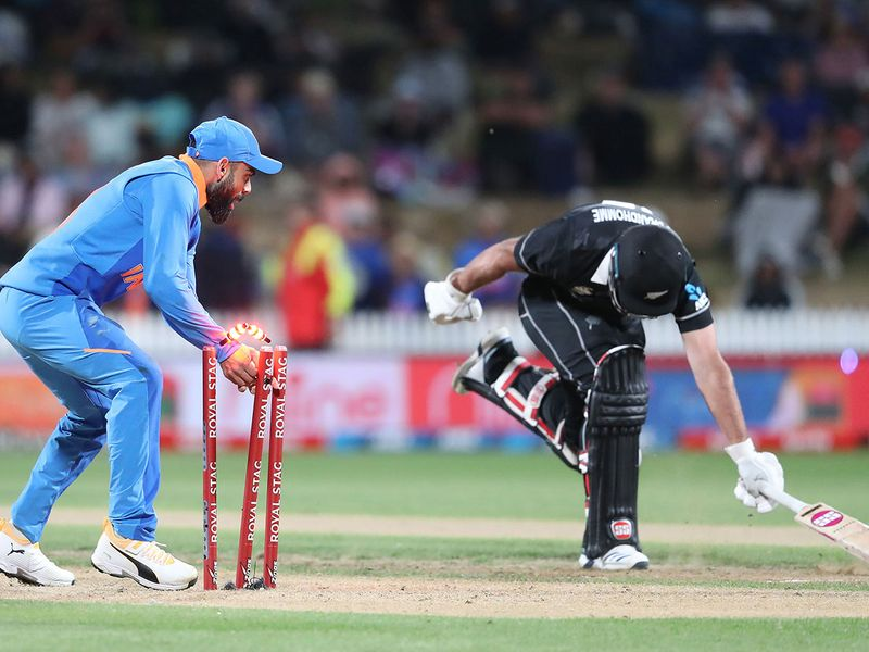 Virat Kohli (L) runs out New Zealand's Colin de Grandhomme