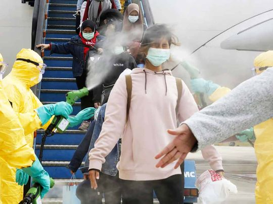 Indonesians who arrived from Wuhan, China, are sprayed with antiseptic at Hang Nadim Airport in Batam, Indonesia.