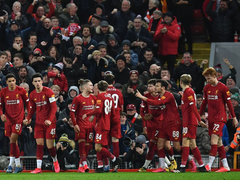 Liverpool players celebrate taking the lead through an own-goal during the English FA Cup fourth round reply football match between Liverpool and Shrewsbury Town at Anfield in Liverpool, north west England on February 4, 2020