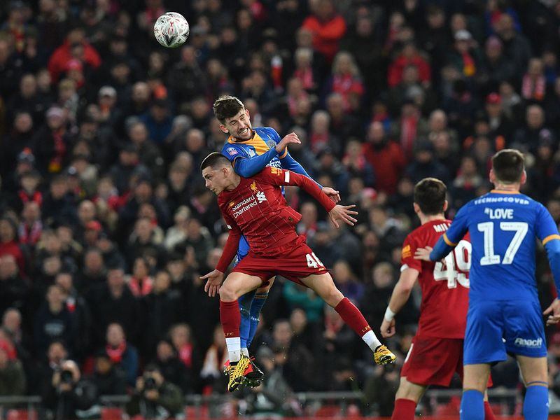 Shrewsbury Town's English striker Callum Lang (up) wins a header from Liverpool's English defender Adam Lewis