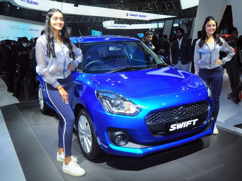 The show features more than 15 start-ups, telecom, alternate fuel, electric vehicle and social media firms. Above: Models pose next to a Maruti Suzuki Swift Hybrid, at the Auto Expo