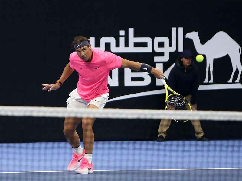 Rafael Nadal of Spain returns the ball to retired compatriot David Ferrer (unseen) during an exhibition game to inaugurate the Rafa Nadal Academy Kuwait, at Shaikh Jaber Al Abdullah Al Jaber Al Sabah International Tennis Complex in the Kuwaiti capital, on February 5, 2020.  / AFP / Yasser Al-Zayyat