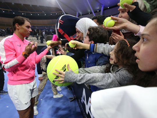Rafael Nadal of Spain signs autographs for fans after an exhibition game to inaugurate the Rafa Nadal Academy Kuwait, at Shaikh Jaber Al Abdullah Al Jaber Al Sabah International Tennis Complex in the Kuwaiti capital, on February 5, 2020.  / AFP / Yasser Al-Zayyat