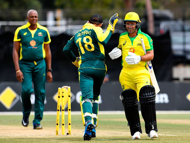 Former Australian player Justin Langer (R) walks off after been bowled by former West Indies player Courtney Walsh (L) as former Australian player Adam Gilchrist (C) looks on