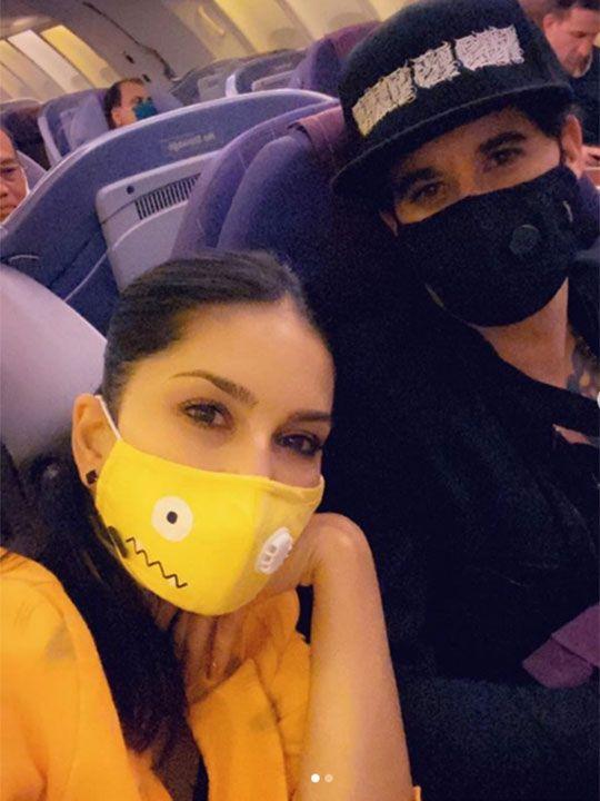 Sunny, accompanied by her husband Daniel Weber wearing masks