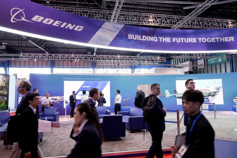 Visitors walk past the Boeing Booth during the opening trade day of the Singapore Airshow.