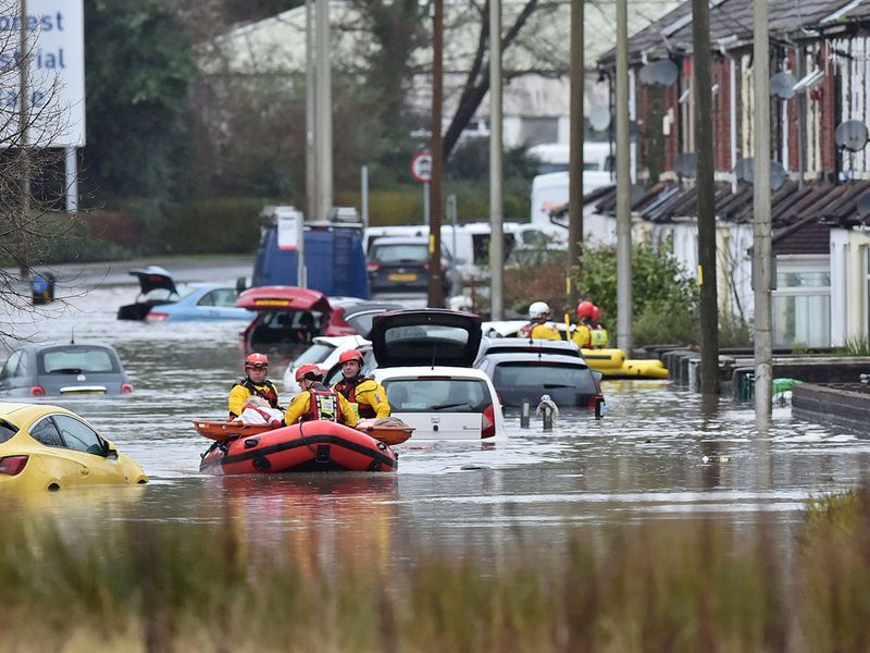 A member of the public is rescued after flooding in Nantgarw, Wales.
