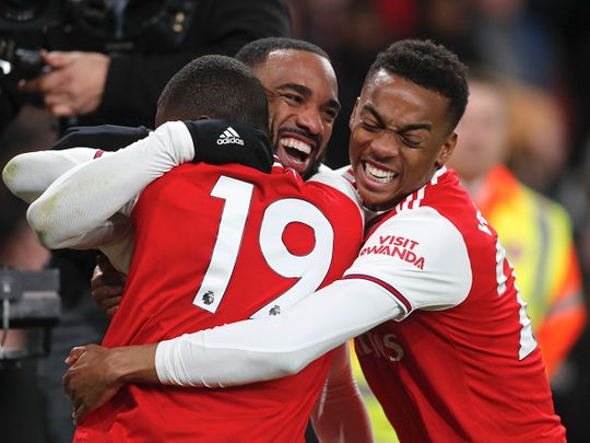 Arsenal's Alexandre Lacazette, center, celebrates after scoring his side's fourth goal during the English Premier League soccer match between Arsenal and Newcastle