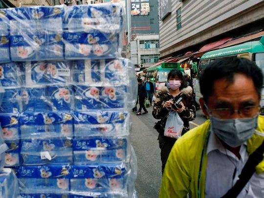 People wear masks as they walk past rolls of toilet paper at a market, following the outbreak of a new coronavirus, in Hong Kong, China February 8, 2020.