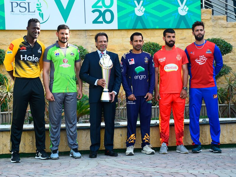 Pakistan's former squash world champion Jahangir Khan holds the PSL trophy along with captains of five participating teams (from left) Darren Sammy, Sohail Akhtar, Sarfaraz Ahmed, Shadab Khan and Imad Wasim at the National Stadium in Karachi, Pakistan, Wednesday, Feb. 19, 2020. Pakistan's premier domestic Twenty20 cricket league begins from Thursday with the final scheduled to be played at Lahore on March 22, 2020. (AP Photo/Fareed Khan)