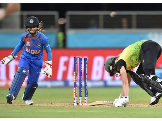 Australia's Ellyse Perry (R) is bowled on her first ball by India's Poonam Yadav during the opening match of the women's Twenty20 World Cup cricket tournament at the Sydney Showground in Sydney on February 21, 2020. --