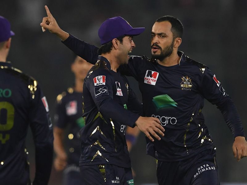 Mohammad Nawaz (R) of Quetta Gladiators celebrates with teammate Ahmed Shehzad (C) after taking the wicket of Colin Munro of Islamabad United during the Pakistan Super League (PSL) Twenty20 cricket match between Quetta Gladiators and Islamabad United at The National Cricket Stadium in Karachi on February