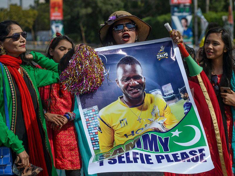 Spectators carry a poster featuring an image of Peshawar Zalmi's team captain Darren Sammy outside the National Cricket Stadium in Karachi on February 21, 2020, ahead of the start of the Pakistan Super League (PSL) T20 cricket match between Peshawar Zalmi and Karachi Kings.  / AFP / Rizwan TABASSUM