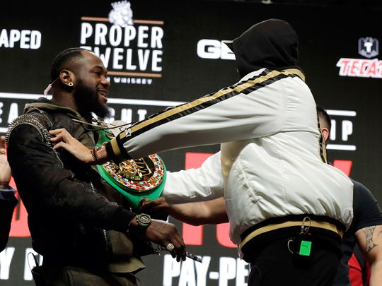 Tyson Fury, right, shoves Deontay Wilder during a face off for photographers at a news conference for their upcoming WBC heavyweight championship boxing match on Wednesday