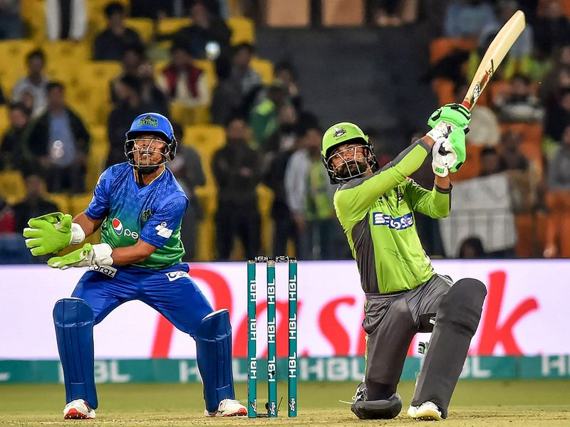 Lahore Qalandars' Mohammad Hafeez (R) plays a shot as Multan Sultans' Zeeshan Ashraf looks on during the Pakistan Super League (PSL) T20 cricket match between Multan Sultans and Lahore Qalandars at the Gaddafi Cricket Stadium in Lahore on February 21, 2020.  / AFP / Arif ALI