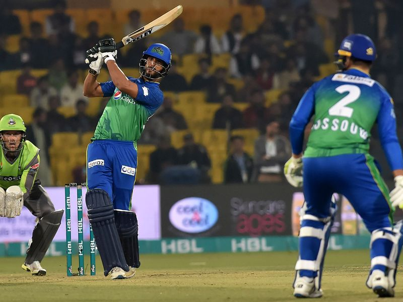 Multan Sultans's Shan Masood (2L) hits a shot as Lahore Qalandars's wicketkeeper Dane Vilas (L) looks on during the Pakistan Super League (PSL) Twenty20 cricket match between Multan Sultans and Lahore Qalandars at The Gaddafi Cricket Stadium in Lahore on February 21, 2020.  / AFP / Arif ALI
