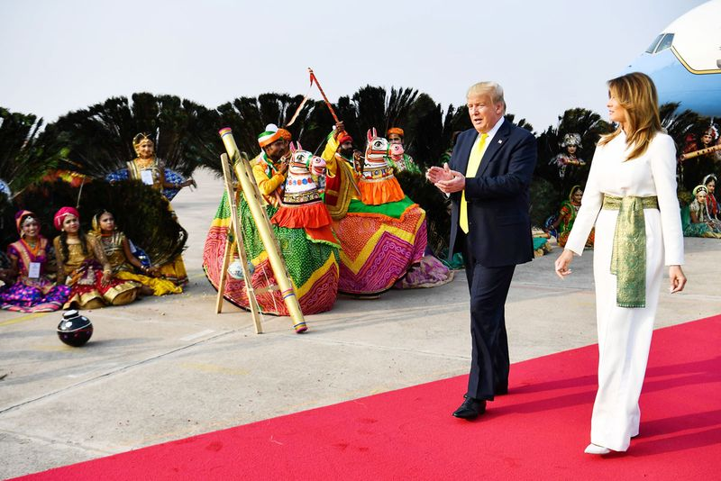 Donald Trump and Melania Trump are greeted by performers wearing traditional costumes as they arrive at Agra Air Base.