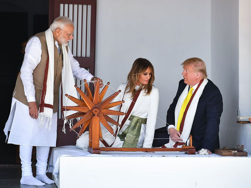 Donald Trump and Melania Trump listen to Narendra Modi (L) as they sit next to a charkha, or spinning wheel, during their visit at Gandhi Ashram in Ahmedabad on February 24, 2020.