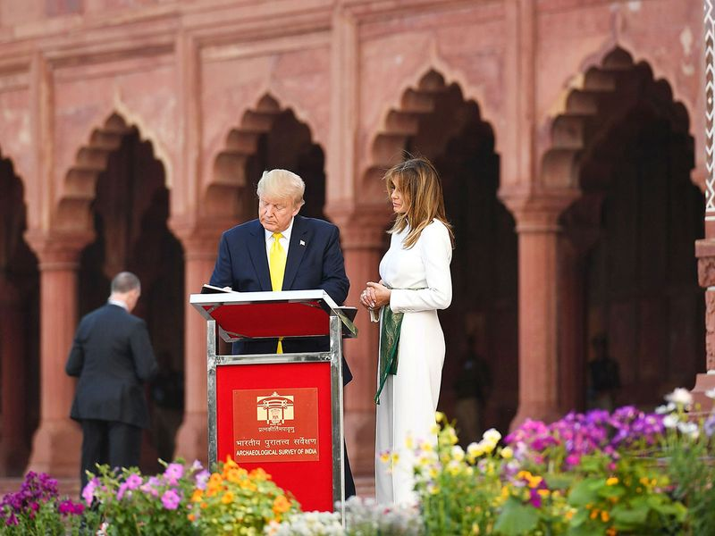 Donald Trump signs a guest book as Melania Trump looks on