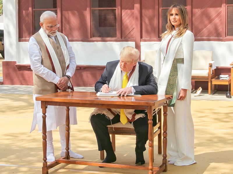 Donald Trump signs the visitors book as Melania Trump and Narendra Modi (L) look on during their visit at Gandhi Ashram in Ahmedabad.