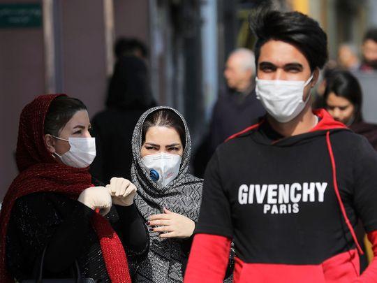 Pedestrians wear masks to help guard against the Coronavirus, in downtown Tehran.