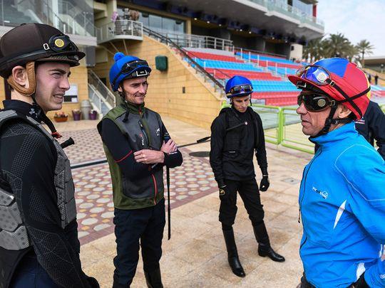 Frankie Dettori, right, speaks with jockeys at the track in Riyadh