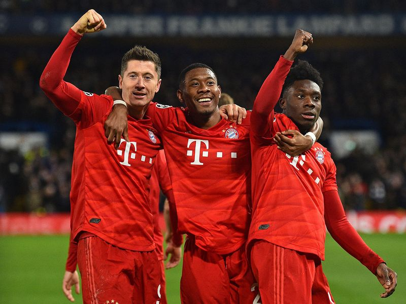 TOPSHOT - Bayern Munich's Polish striker Robert Lewandowski (L) celebrates with Bayern Munich's Austrian defender David Alaba (C) and Bayern Munich's Canadian midfielder Alphonso Davies (R) after scoring their third goal during the UEFA Champion's League round of 16 first leg football match between Chelsea and Bayern Munich at Stamford Bridge in London on February 25, 2020.   / AFP / Glyn KIRK