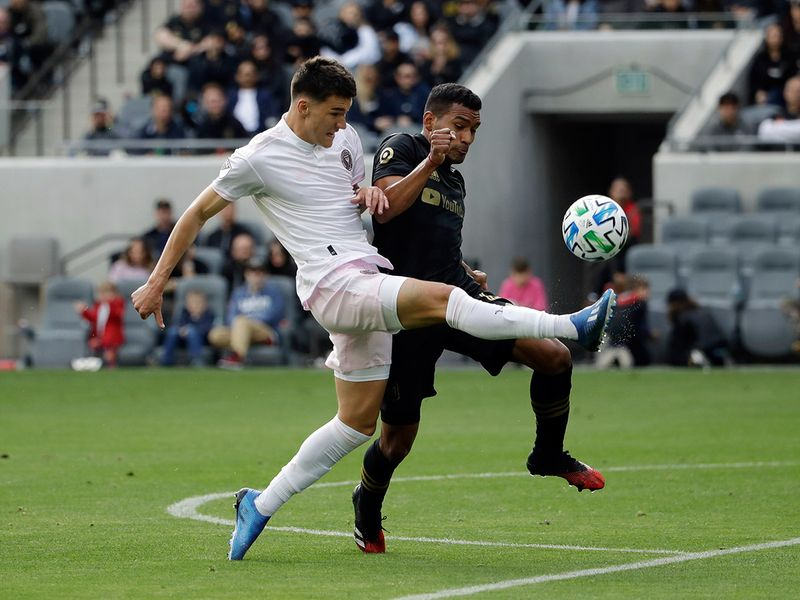 Inter Miami CF's Robbie Robinson, left, shoots as Los Angeles FC's Eddie Segura defends during the first half of an MLS soccer match Sunday, March 1, 2020, in Los Angeles. (AP Photo/Marcio Jose Sanchez)